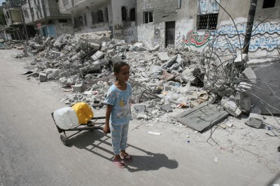 On 19 July 2014 in the State of Palestine, passing the rubble of homes destroyed in an Israeli air strike, a girl uses a hand truck to transport jerrycans filled with water, in the town of Rafah in southern Gaza. Photo: UNICEF/NYHQ2014-0978/El Baba